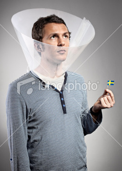 A man wears an elaborate flea collar and holds a tiny Swedish flag